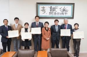 市長表彰と併せこども青少年局長表彰も。表彰された団体、企業の皆さん。林市長(中央)を囲んで、渡邊所長(左)と、西村さん(右)